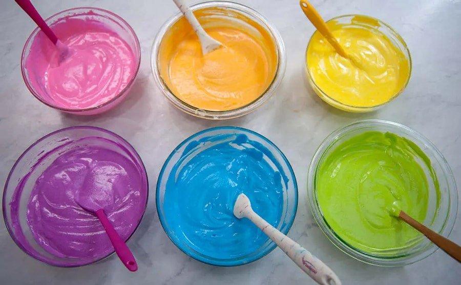 اضافه کردن رنگ خوراکی به خمیر برای درست کردن کیک رنگین کمان
